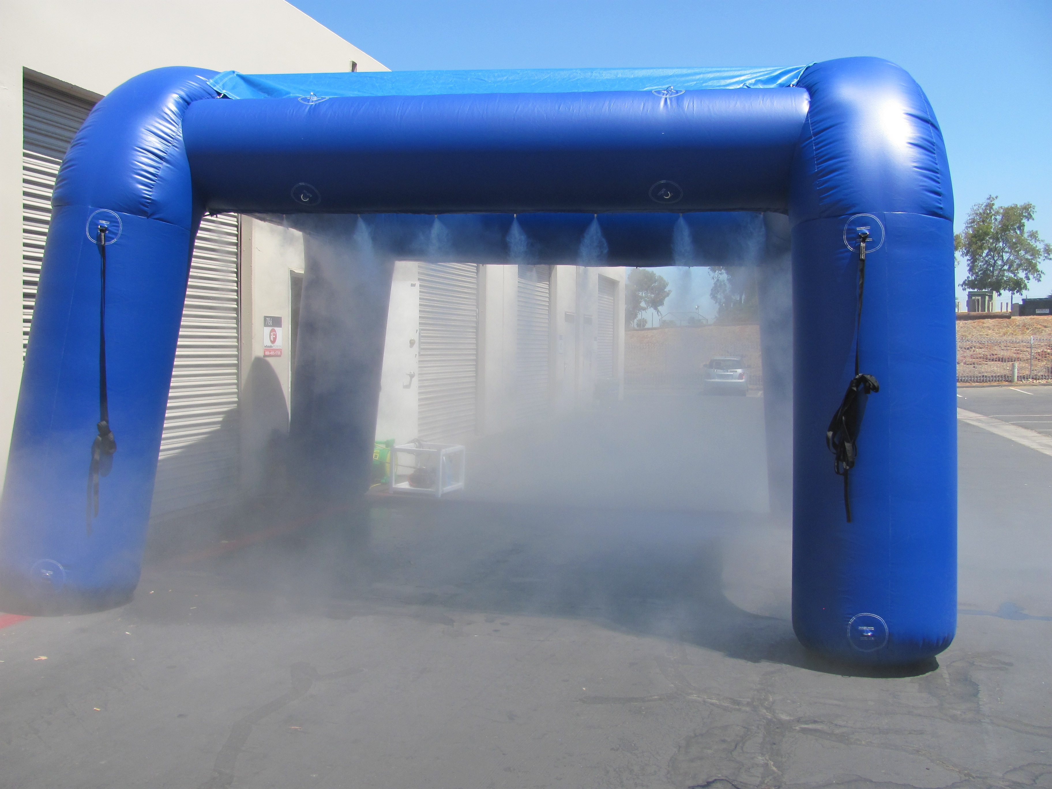 Blue coloured high-pressure oasis misting pavilion producing mist at the empty parking lot.