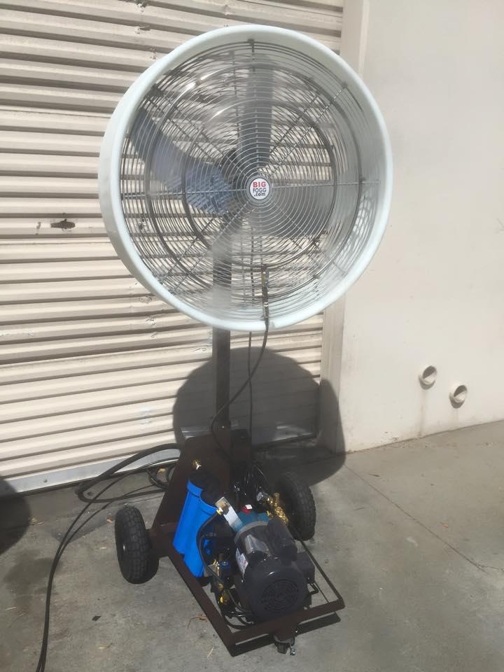 "A 30″ ""Work Zone"" Misting Fan outside a closed white shop shutter"