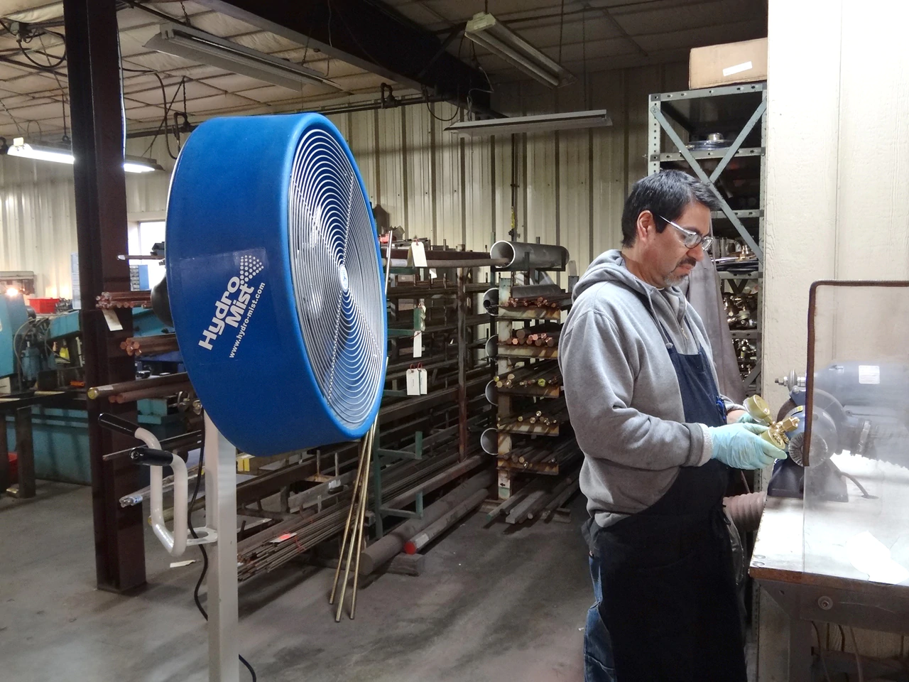 """The """"BOSS"""" Industrial Outdoor /Indoor 24inch Shrouded Oscillating Floor Fan-2 Speeds at a worker in a facotry"""