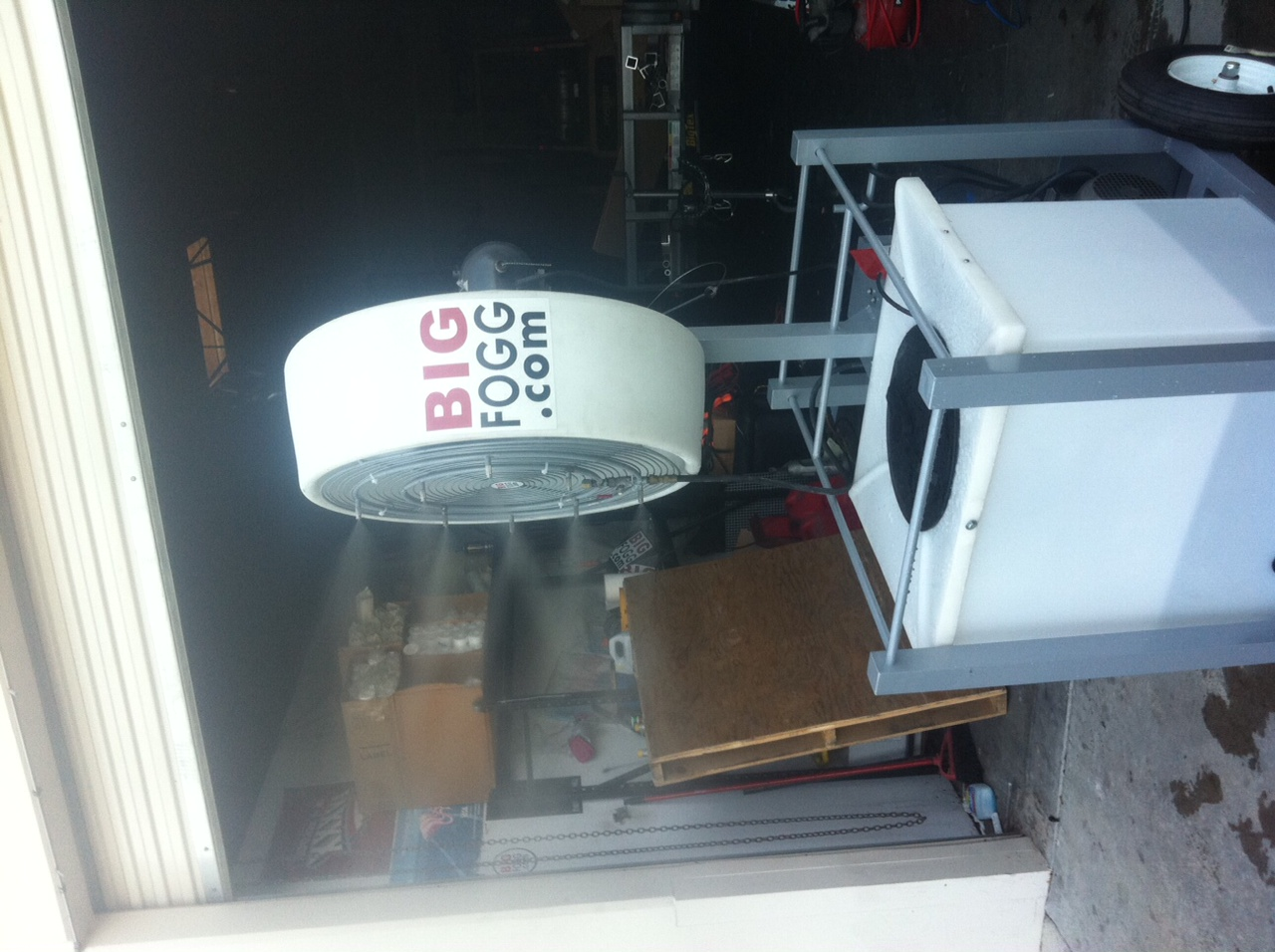 side view of Big Fogg High-Pressure Misting Fan with 40' Gallon Tank outside open garage