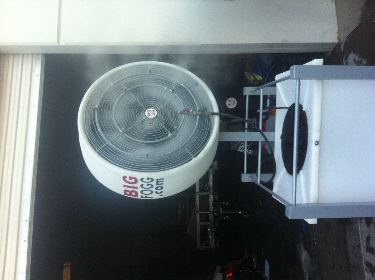 Big Fogg High-Pressure Misting Fan with 40' Gallon Tank outside a garage
